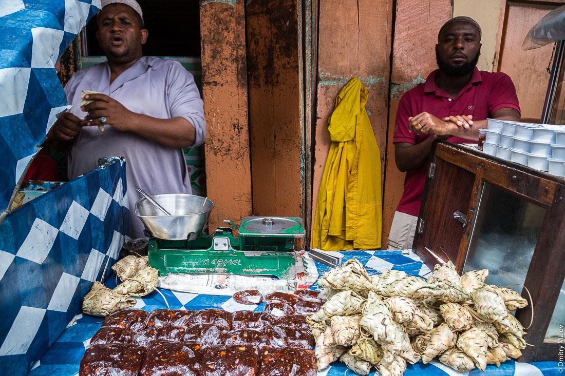 Рынок, два чёрных мужчины-торговца, город Чаки-Чаки, остров Пемба, Занзибар, Танзания. Market, bazaar. Two black men-vendors, Chake-Chake town, Pemba island, Zanzibar, Tanzania
