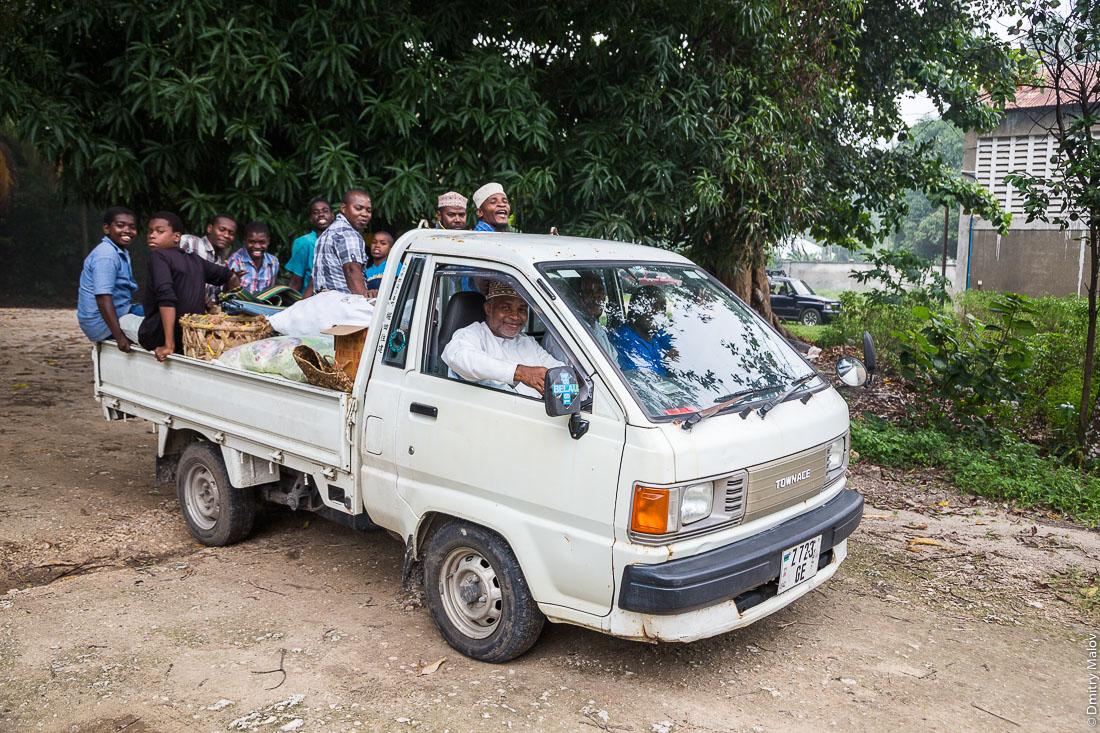 Рабочие завода по перегонке специй в масло, приехали в грузовке, остров Пемба, Занзибар, Танзания. Workes Pemba essential oil Distillery (PEOD) on a pick-up truck, Pemba island, Zanzibar, Tanzania