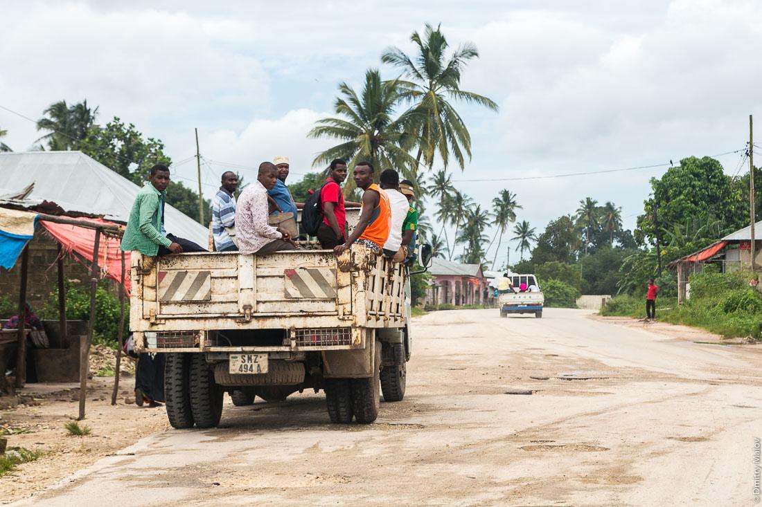 Местные едут в кузове грузовика. Дороги Занзибара, остров Унгуджа, Танзания. Local people riding on a truck. Roads of Zanzibar, Unguja island, Tanzania.