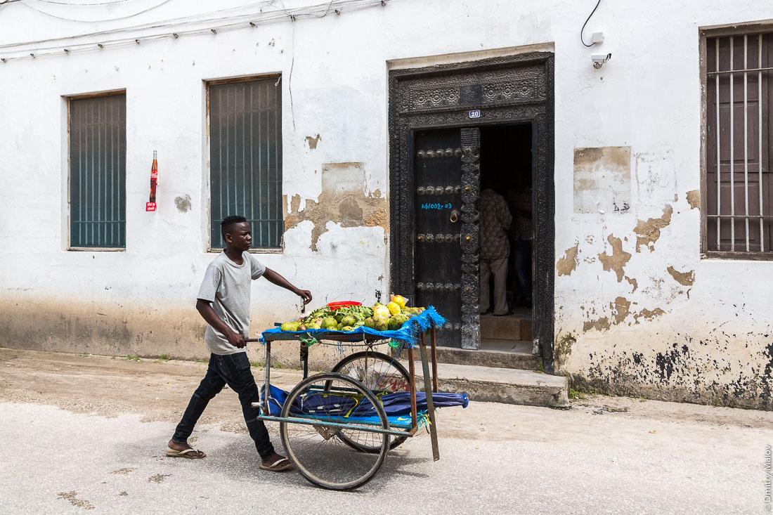 Резные занзибарские двери. Уличный торговец. Каменный город, Занзибар-сити, остров Унгуджа, Танзания. Carved Zanzibar doors. Street vendor. Stone Town, Zanzibar City, Unguja island, Tanzania.