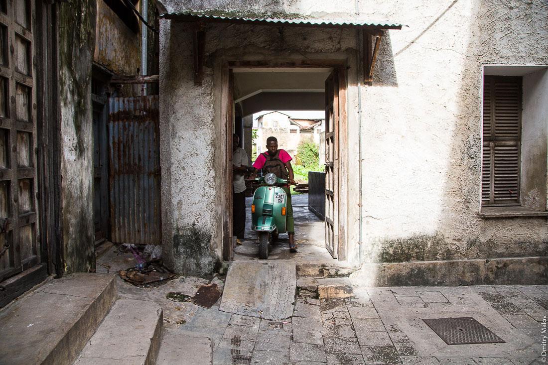 Мотоциклист выезжает из подъезда. Каменный город, старая часть Занзибар-сити, остров Унгуджа, Танзания. A motorcyclist goes out of the building entrance. Stone Town, old town of Zanzibar City, Unguja island, Tanzania