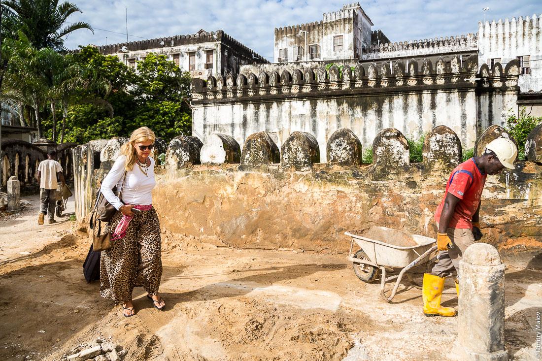 Дворец султана, туристка с чемоданом и два строителя с тачками. Каменный город (Стоун-таун), старая часть Занзибар-сити, остров Унгуджа, Танзания. Sultan's palace, a woman tourist with a suitcase and two builders with wheelbarrows. Stone Town, old town of Zanzibar City, Unguja island, Tanzania.