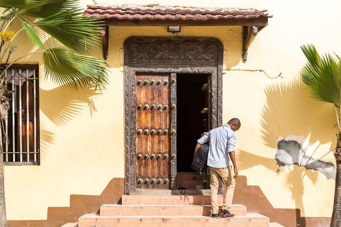 Резные занзибарские двери. Мужчина надевает обувь выходя из мечети. Каменный город (Стоун-таун), старая часть Занзибар-сити, остров Унгуджа, Танзания. A man puts on his shoes leaving the mosque. Carved Zanzibar doors. Arabic doors. Stone Town, old town of Zanzibar City, Unguja island, Tanzania.