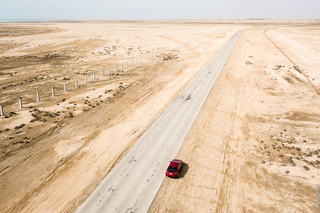Aerial view of desert, asphalt road and a red car, Madinat ash Shamal near Zubarah, Qatar. Фото с дрона, пустыня, красная машина, Зубарах, район Эш-Шамаль, Катар