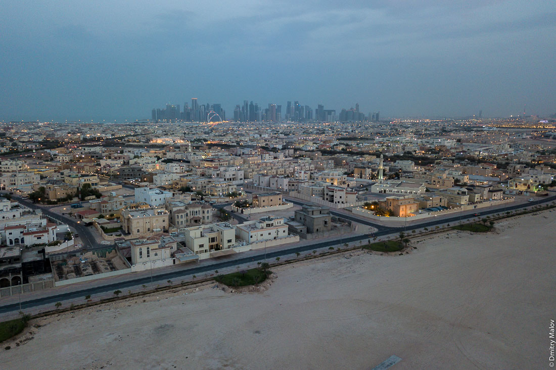 Doha, Qatar - an aerial drone photo of a skyscraper city bordering the desert. Катар, Доха — аэрофотосъемка с дрона города небоскрёбов граничащего с пустыней