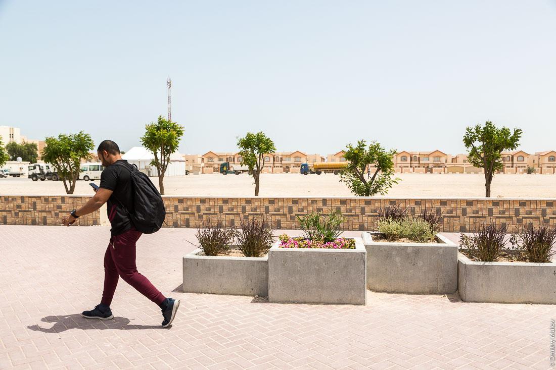 Мужчина идёт по мощенной улице с клумбами, город Аль-Хор (Эль-Хаур), Катар. A man walks along a cobbled tiles street with flower beds, Al Khor city, Qatar.