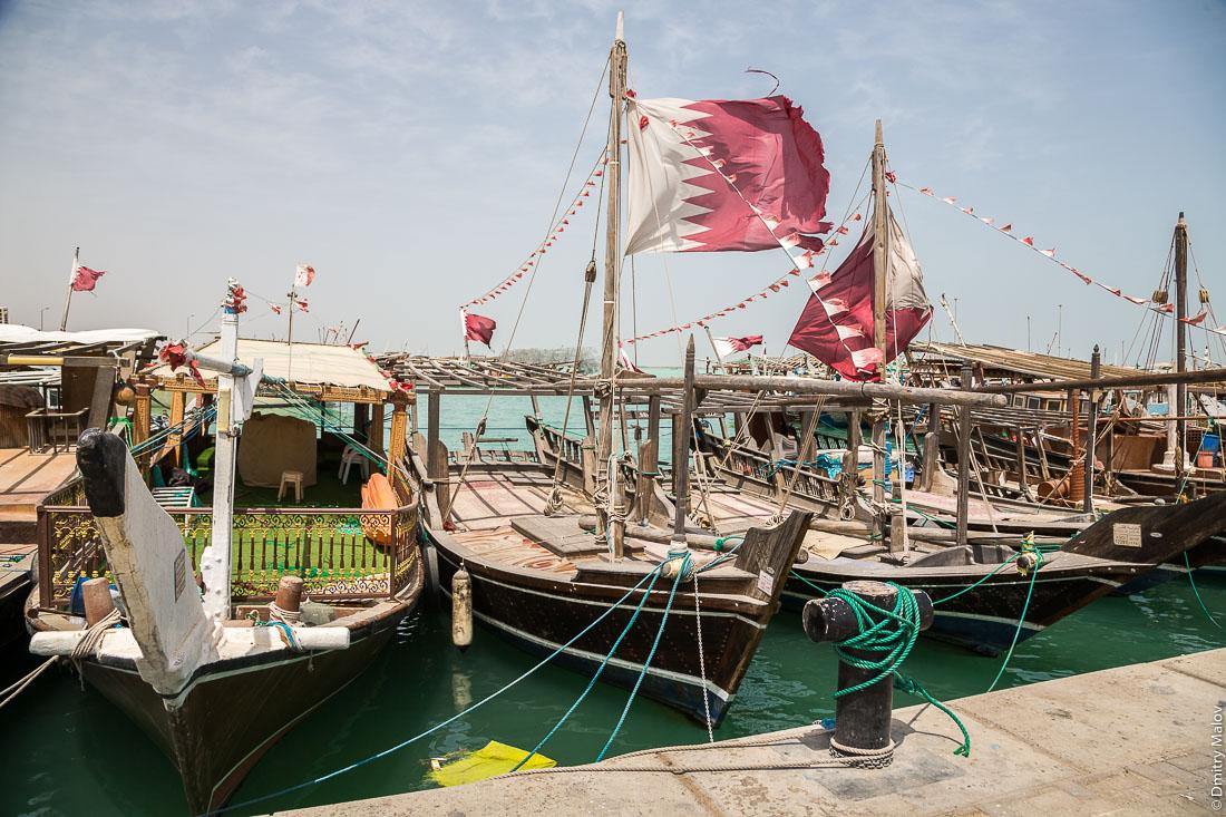 Традиционные арабские рыбацкие лодки дау под флагом Катара в порту города Аль-Хор (Эль-Хаур), Катар. Arab traditional fishing dhow boats displaying Qatar flag in port of Al Khor city, Qatar