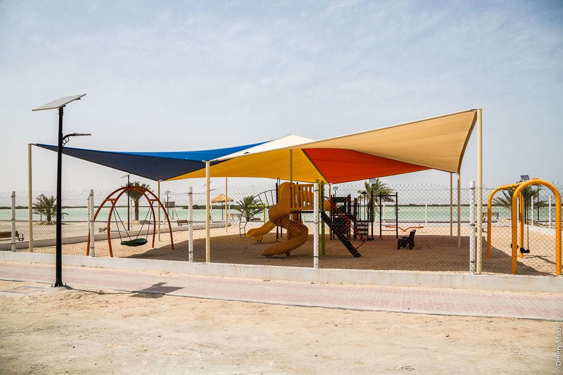 Детская игровая площадка с навесом против солнца. Город Аль Дакира, Катар. Children's playground with tent canopy against the sun. Al Thakhira (Al Dhakira) town, Qatar.