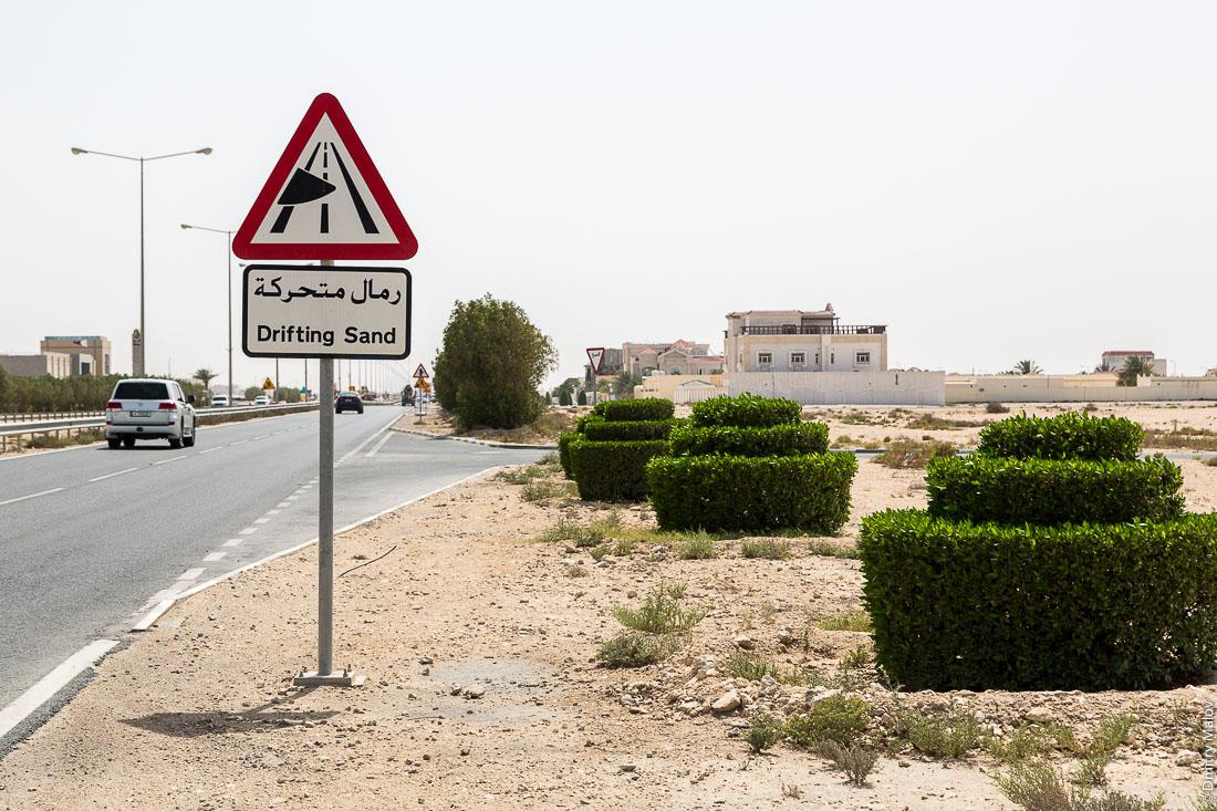 Дорожный знак: Осторожно: Дрейфующий песок. Город Аль Дакира, Катар. Drifting Sand road sign on road of Al Thakhira (Al Dhakira) town, Qatar.