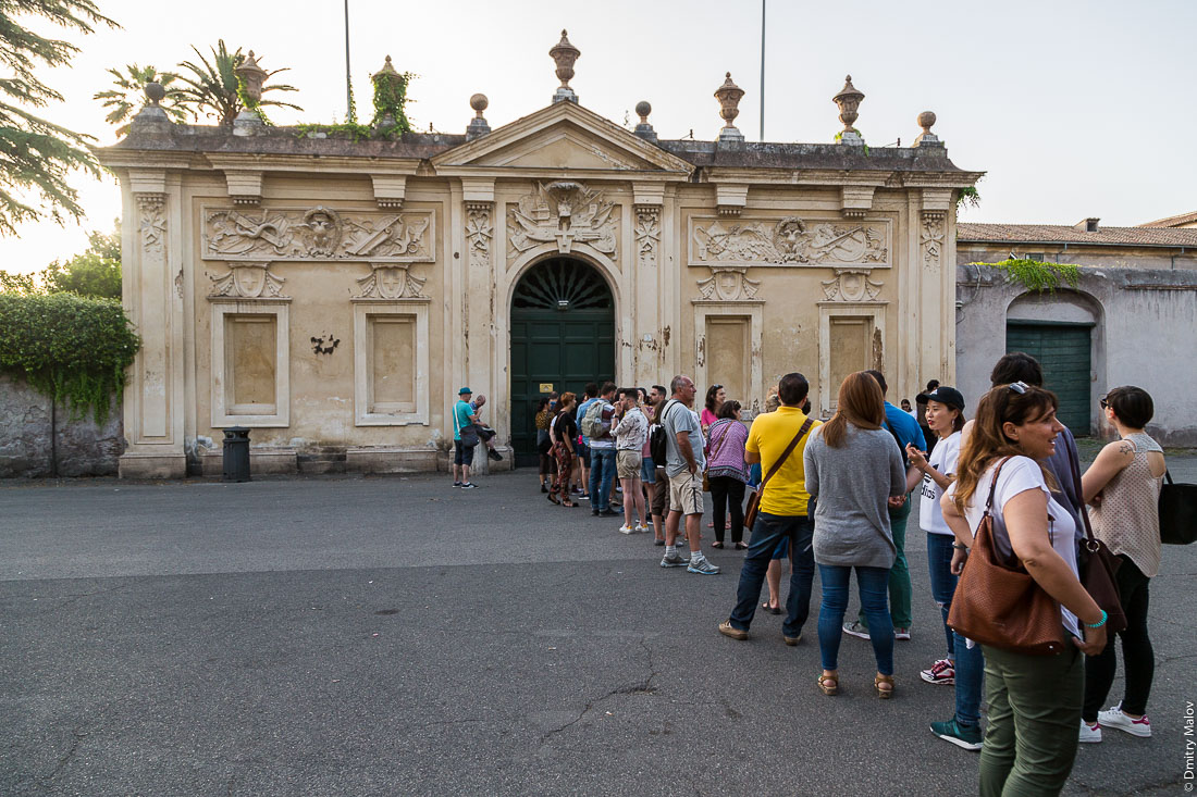 Tourists queuing to sneak peek through the keyhole of Villa del Priorato di Malta (Magistral Villa), piazza dei Cavallieri di Malta, Aventine Hill, Rome. Очередь туристов чтобы заглянуть в замочную скважину Магистральной виллы Мальтийского ордена, пьяцца Кавалльери ди Мальта, холм Авентин, Рим