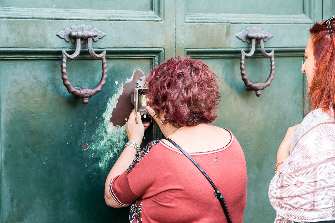 Tourist makes a photo through the keyhole of the gates of Villa del Priorato di Malta (Magistral Villa), piazza dei Cavallieri di Malta, Aventine Hill, Rome. Туристка делает фото через замочную скважину ворот Магистральной виллы Мальтийского ордена, пьяцца Кавалльери ди Мальта, холм Авентин, Рим