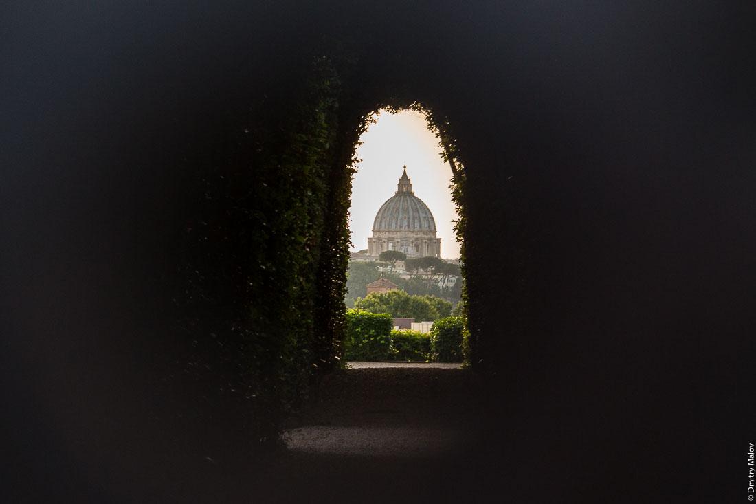 Dome of St. Peter's Basilica, Vatican through the keyhole of the gates of Villa del Priorato di Malta (Magistral Villa), piazza dei Cavallieri di Malta, Aventine Hill, Rome. Купол собора Святого Петра, Ватикан через замочную скважину ворот Магистральной виллы Мальтийского ордена, пьяцца Кавалльери ди Мальта, холм Авентин, Рим