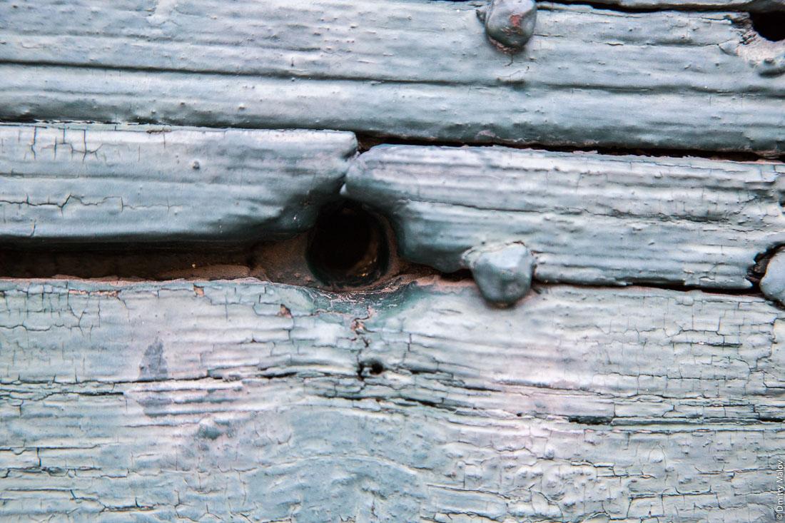 A keyhole in a old blue wooden gates. Замочная скважина в старых голубых деревянных воротах.
