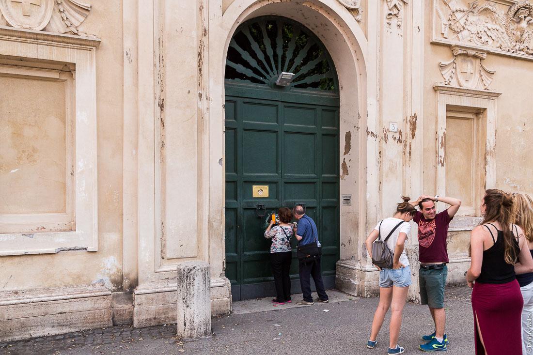 Tourists queuing to sneak peek through the keyhole of the gates of Villa del Priorato di Malta (Magistral Villa), piazza dei Cavallieri di Malta, Aventine Hill, Rome. Очередь туристов чтобы заглянуть в замочную скважину ворот Магистральной виллы Мальтийского ордена, пьяцца Кавалльери ди Мальта, холм Авентин, Рим