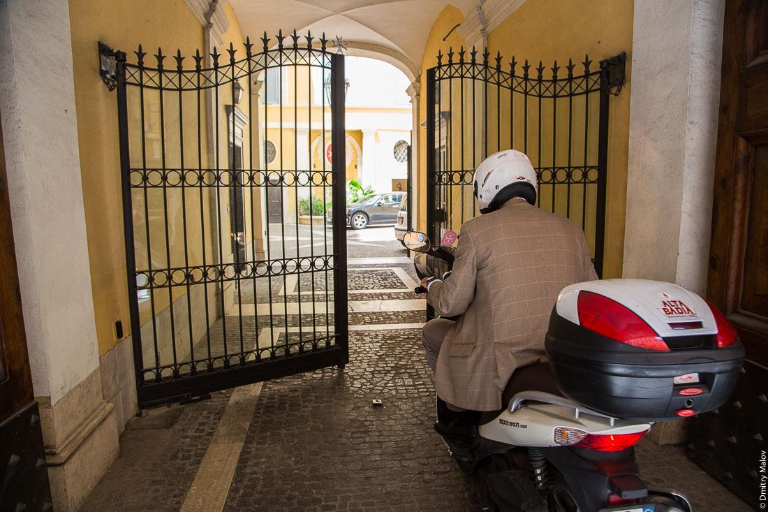 Мужчина в костюме на мотороллере и ворота Мальтийского дворца, виа Кондотти, 68, Рим, Италия. A man in a suite on scooter and the gates of Palazzo Magistrale, Palazzo di Malta, Via dei Condotti 68, Rome, Italy