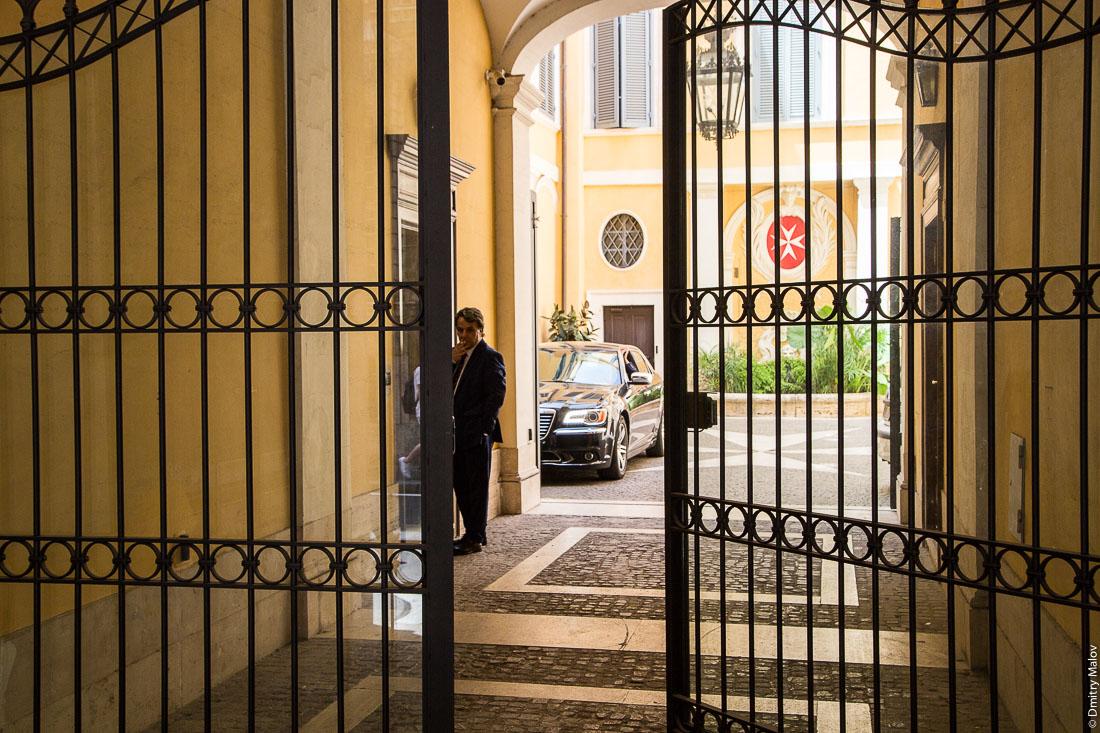 Мужчина в костюме и ворота Мальтийского дворца, виа Кондотти, 68, Рим, Италия. A man in a suite and the gates of Palazzo Magistrale, Palazzo di Malta, Via dei Condotti 68, Rome, Italy