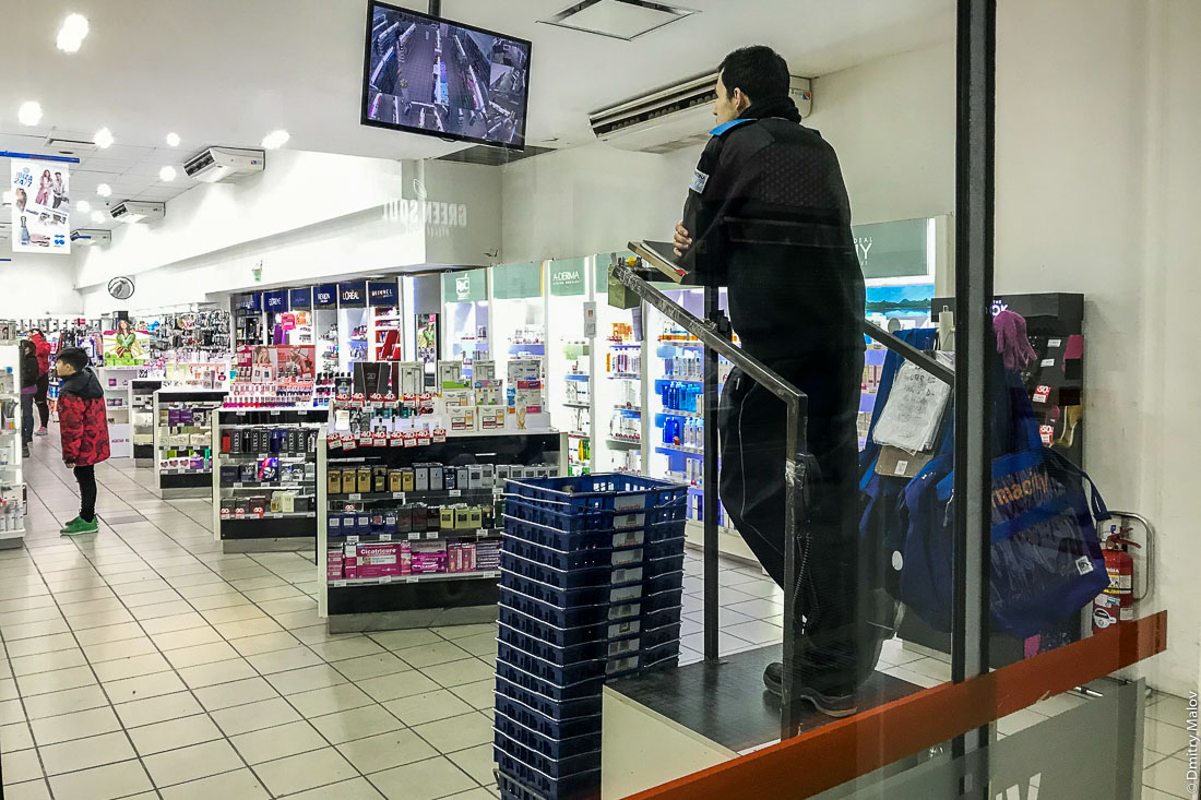 Охранник с поднятой платформы следит за магазином, Буэнос-Айрес, Аргентина. A guard on an elevated platform is watching over the store, Buenos Aires, Argentina.