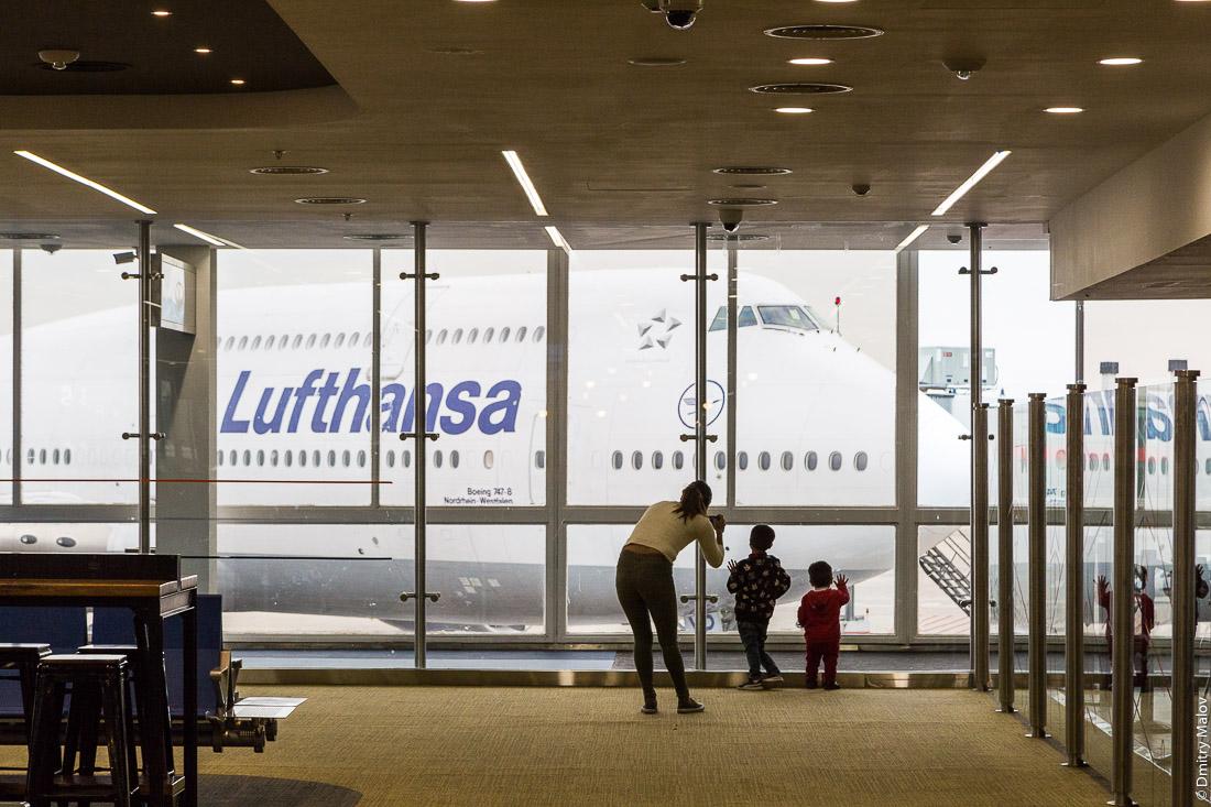 A woman takes a photo of children waving goodbye to Lufthansa Boeing 747-8 (D-ABYP) in Ezeiza International Airport (IATA:EZE), Buenos Aires, Argentina. Женщина фотографирует как дети машут пока-пока. Боинг 747-8 (D-ABYP) авиакомпании Люфтганза в международном аэропорту Эсейса имени министра Пистарини (ИАТА: EZE), Буэнос-Айрес, Аргентина.