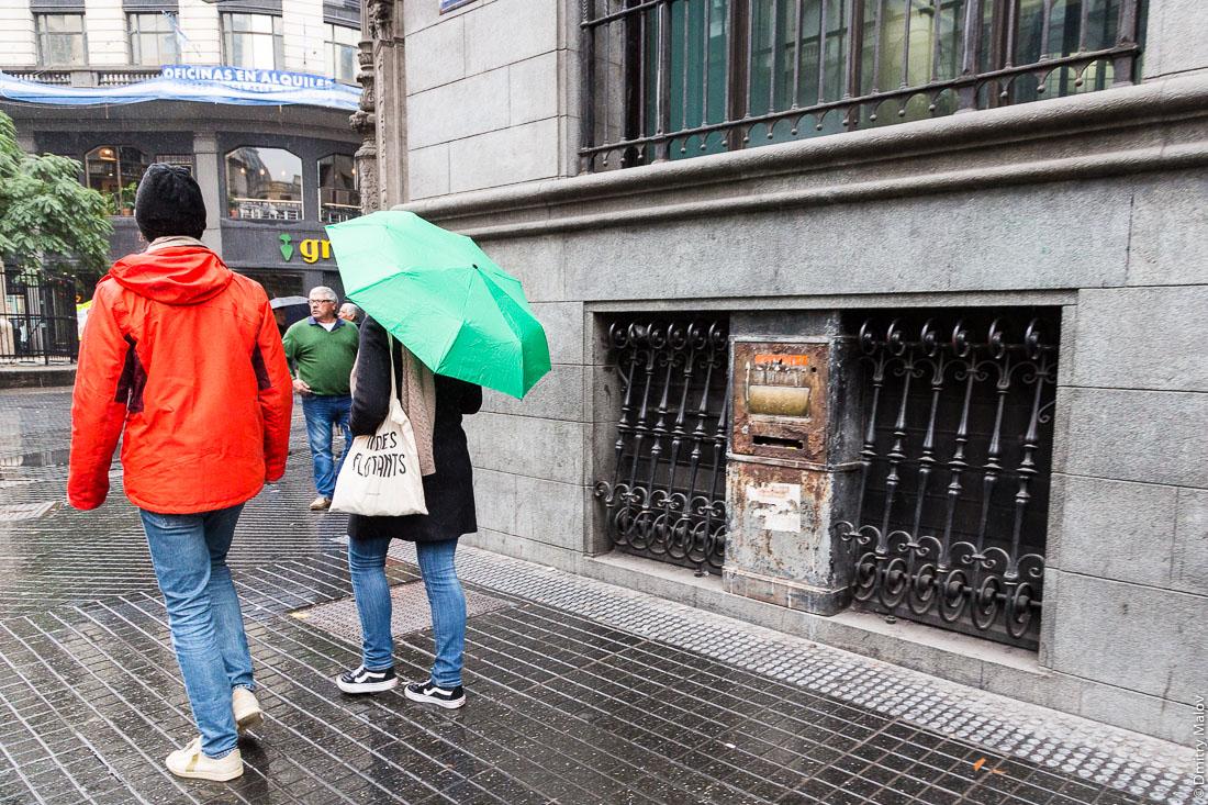 Пара спешит под зонтом под дождём мимо старого ржавого почтового ящика в центре Буэнос-Айреса, Аргентина. A couple hurries under an umbrella in the rain past an old rusty mailbox in the center of Buenos Aires, Argentina.
