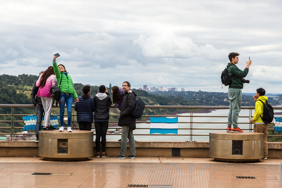 Argentinian tourists taking selfies with Ciudad del Este in background at Iguazú and Paraná rivers confluence. Tres Fronteras, Triple Frontier, La Triple Frontera of Paraguay, Argentina, Brazil. Аргентинские туристы делают селфи на фоне города Сьюдад-дель-Эсте и слияния рек Игуасу и Параны. Тройная граница Парагвая, Аргентины и Бразилии.