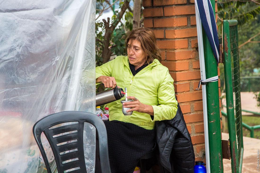 Местная женщина наливает кипяток в калебасу для мате, La Triple Frontera, Пуэрто-Игуасу, Аргентина. A local woman pours boiling water from a thermos into mate gourd, La Triple Frontera, Puerto Iguazu, Argentina.