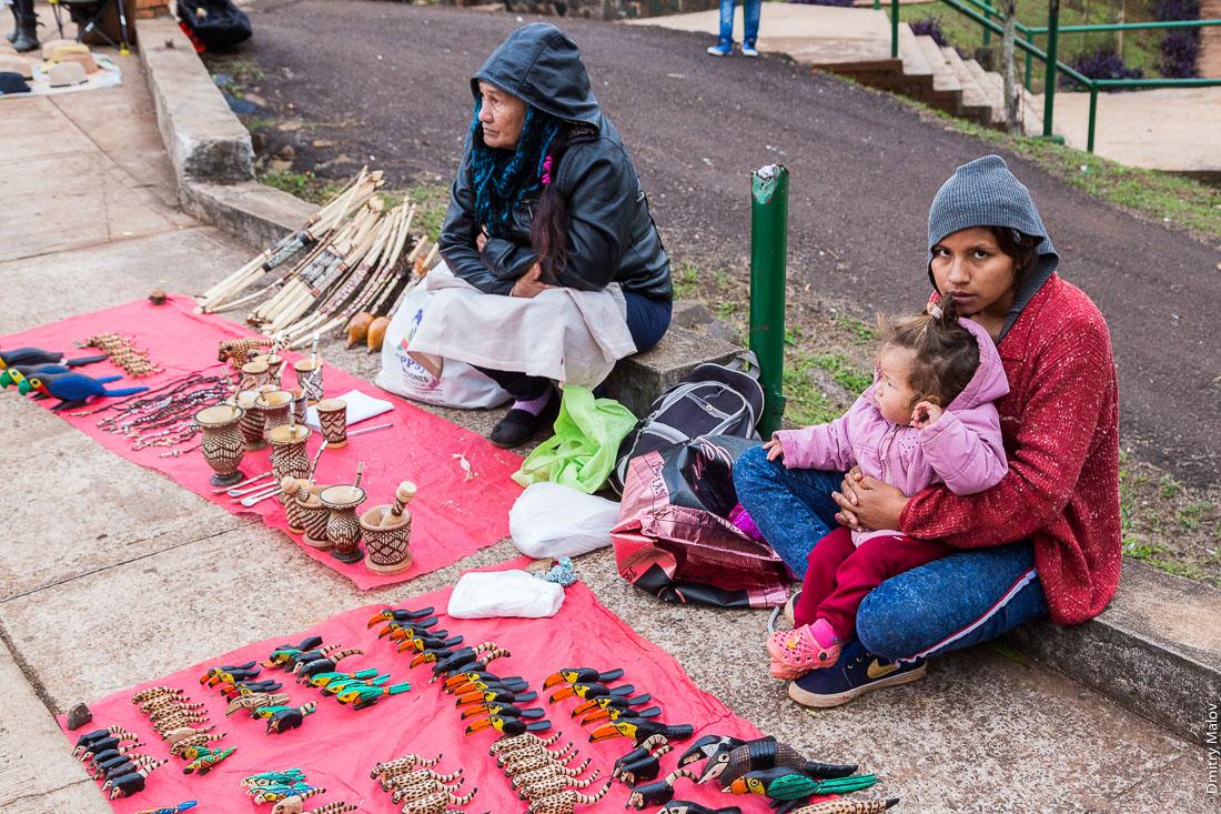 Индейцы гуарани - пожилая женщина и молодая женщина с ребёнком - продают сувениры, парк La Triple Frontera, Пуэрто-Игуасу, Аргентина. Guarani Indians - an elderly woman and a young woman with a child - sell souvenirs, La Triple Frontera Park, Puerto Iguazú, Argentina.