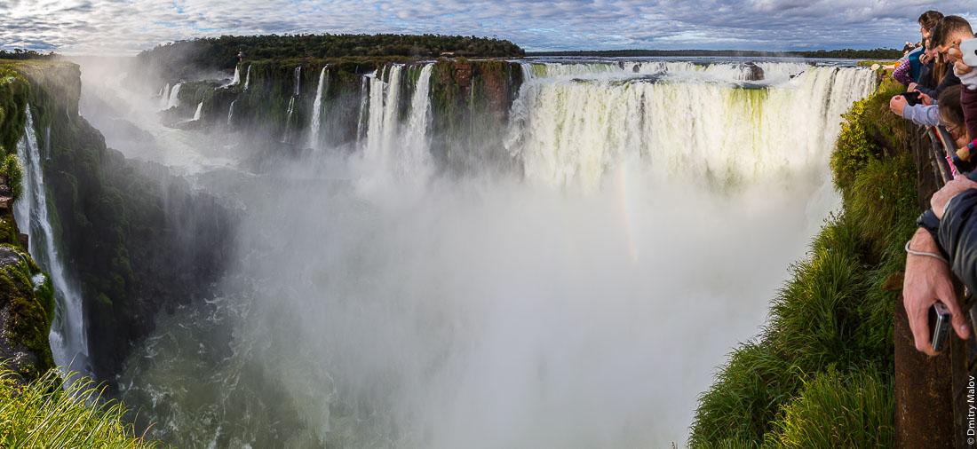 Туристы смотрят на водопад Глотка дьявола, водопад Игуасу, Бразилия, Аргентина. Tourists at canopy boardwalk at Garganta del Diablo. Devil's Throat, Iguazu Falls, Brazil, Argentina.