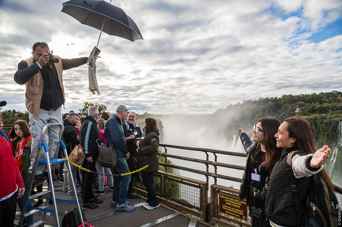 Туристы фотографируются у лицензированного фотографа. Водопад Глотка дьявола, водопад Игуасу, Бразилия, Аргентина. Tourists and authorized photographer. Garganta del Diablo. Devil's Throat, Iguazu Falls, Brazil, Argentina.