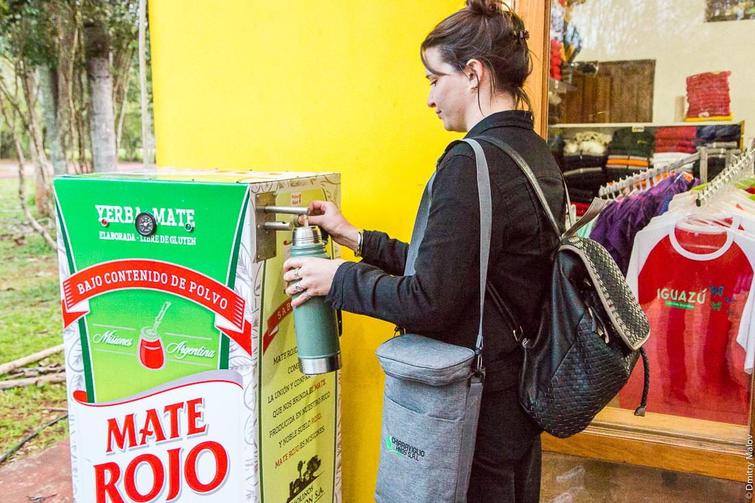 Бредированный производителем мате киоск с кипятком, женщина наливает кипяток для мате в термос. Национальный парк Водопады Игуасу, Аргентина. Mate vendor Branded machine with boiling water, a woman pours boiling water for mate to her thermos. Iguazu Falls National Park, Argentina.