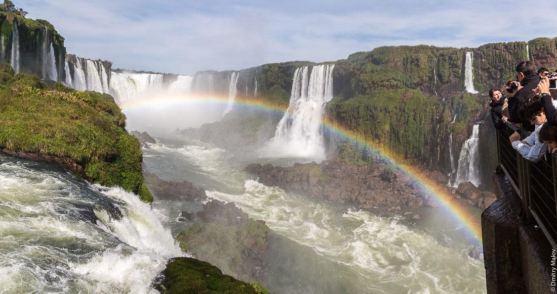 Туристы смотрят на водопад Глотка дьявола, водопад Игуасу, бразильская сторона. Tourists at canopy boardwalk at Garganta del Diablo. Devil's Throat, Iguazu Falls, Brazilian side.