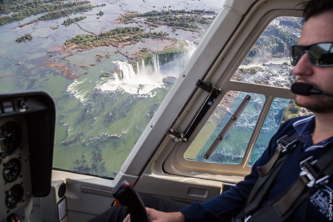 Водоподы Игуасу, Глотка дьявола из кабины вертолёта, пилот вертолёта. Аэрофотосъемка. Бразилия, Аргентина. Garganta del Diablo, Devil's Throat, Iguazu Falls, view from Helicopter cockpit and a pilot. Aerial photo. Brazil, Argentina.