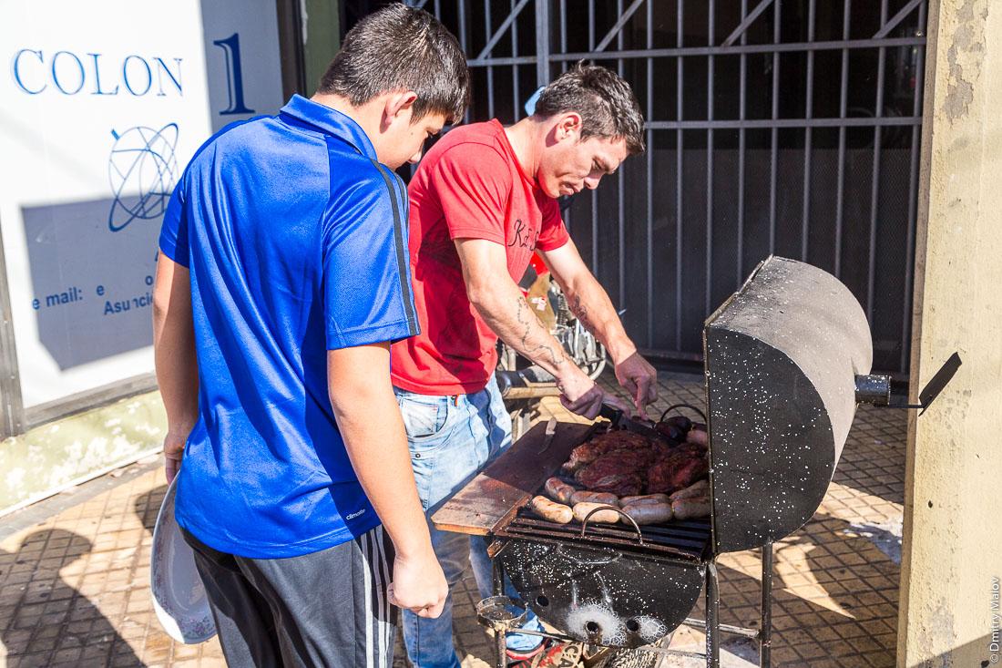 Мужчина с парнем жарят парилью (гриль). Асунсьон, Парагвай. A man and a boy prepare parrilla (grill). Streets, Asuncion city, Paraguay