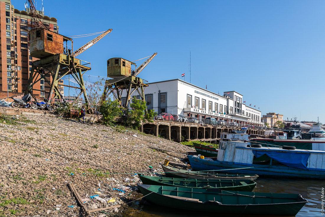 View of abandoned port cranes, customs HQ and fleet of boats on embankment of Paraguay river, Latin American capital of Asuncion city, Paraguay. Вид заброшенных портовых кранов, штаб-квартиры таможник и пришвартованных лодок на набережной реки Парагвай, латиноамериканская столица город Асунсьон, Парагвай.