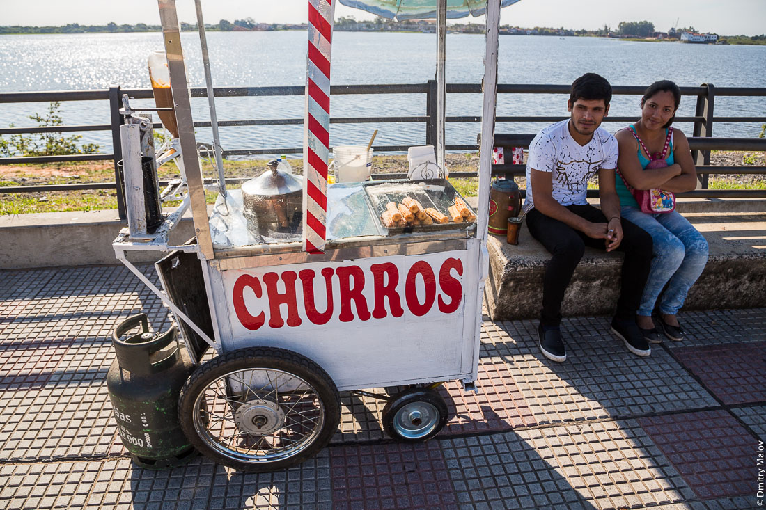 View of two people — a guy and a girl, — and a churros stall on embankment of Paraguay river, Latin American capital of Asuncion city, Paraguay. Парень и девушка жарят и продают чурос на набережной реки Парагвай, латиноамериканская столица город Асунсьон, Парагвай.