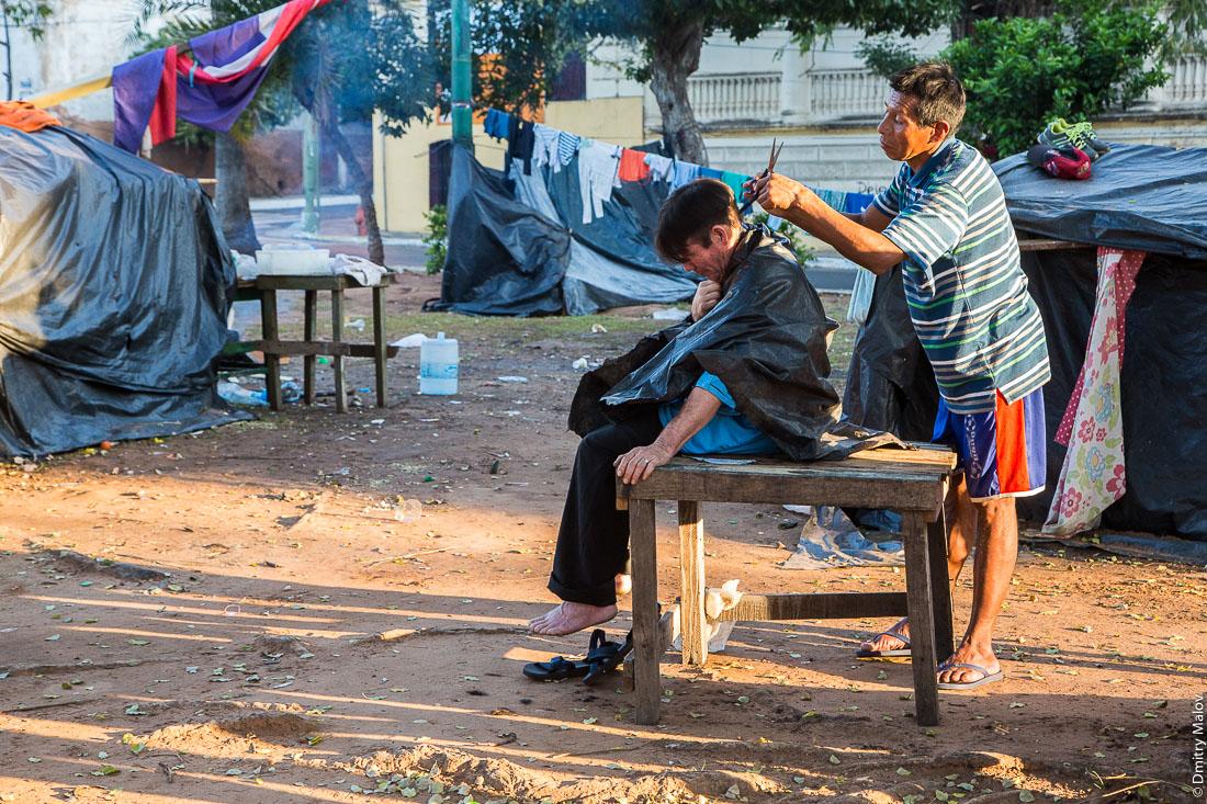 Парикмахер работает в трущобном лагере протестующих индейцев на Пласа-де-Армас, Асунсьон, Парагвай. A hairdresser works in a slum camp of Indian protesters on Plaza de Armas, Asuncion, Paraguay.