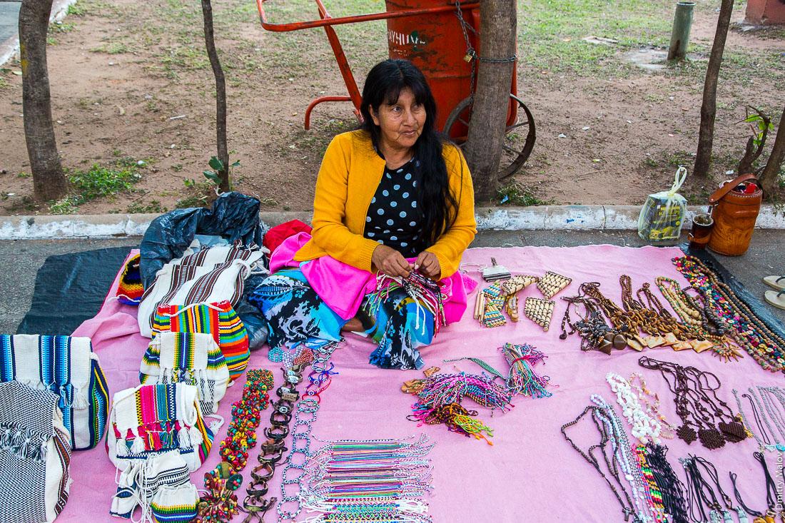 Индейская женщина плетёт и продает сувениры и фенечки. На центральной улице, Асунсьон, Парагвай. An Indian woman knits and sells souvenirs and bracelets. On a central street, Asunción, Paraguay.