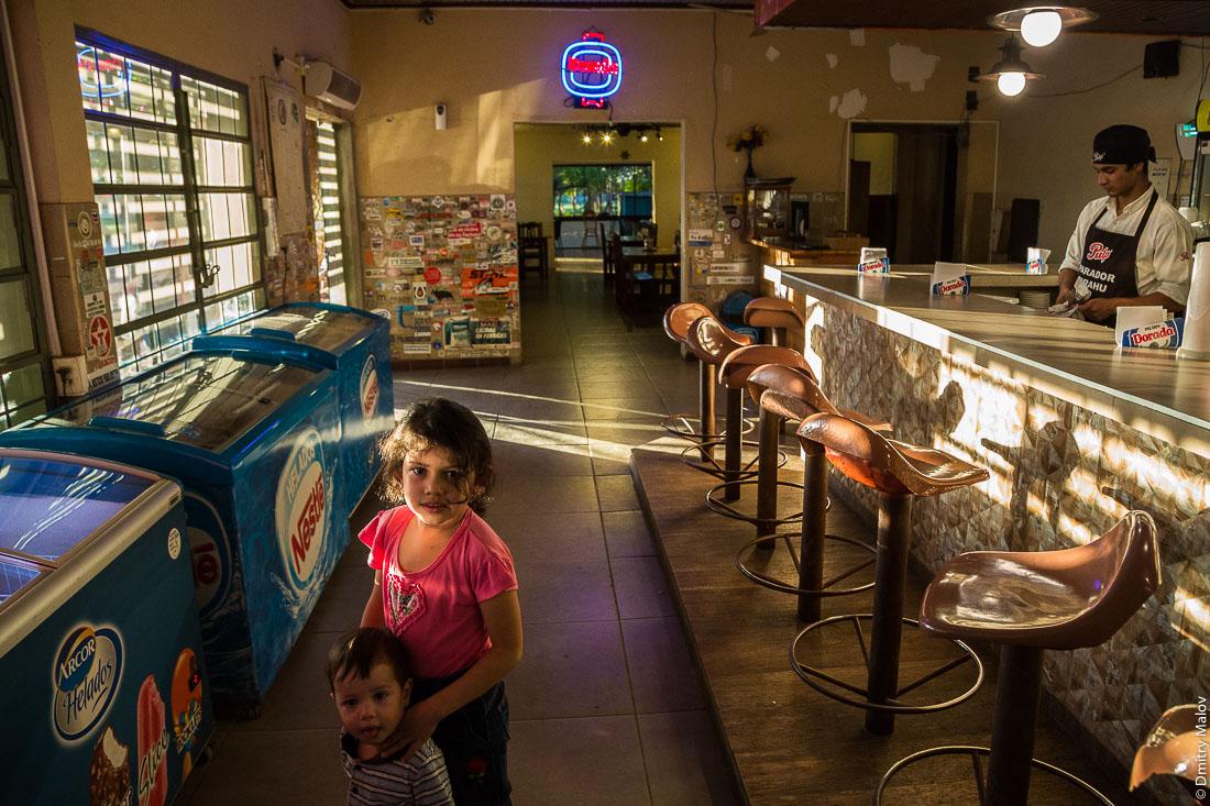 Девочка душит мальчика в придорожном дайнере, Рута Трансчако, Гран-Чако, Парагвай. A girl strangling a boy in a diner along the highway number 9 Ruta Transchaco, Gran Chaco, Paraguay.