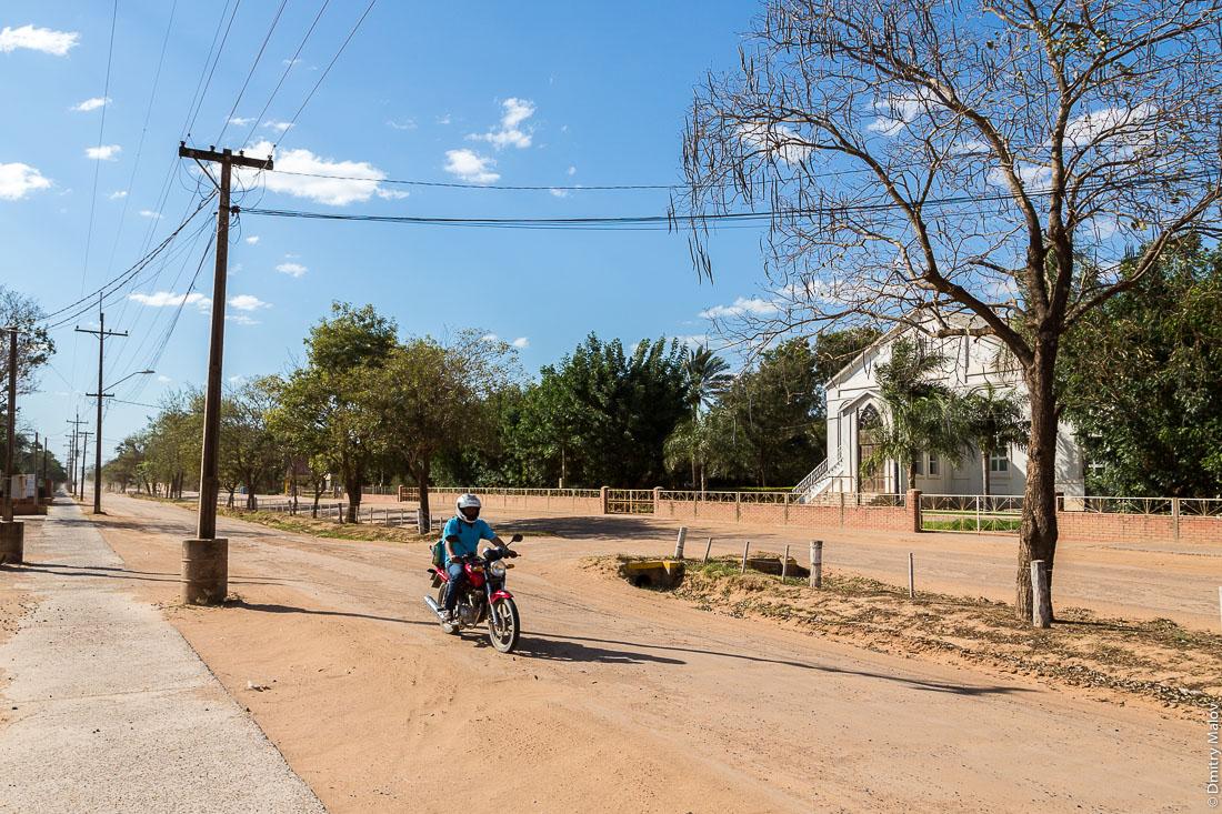 Мотоциклист в шлеме несётся мимо церкви по пыльному песчаному бульвару. Центр города Филадельфия, Гран-Чако, Парагвай. Filadelfia city centre, Gran Chaco, Paraguay. A motorcyclist in a helmet rushes past the church along a dusty sandy boulevard.