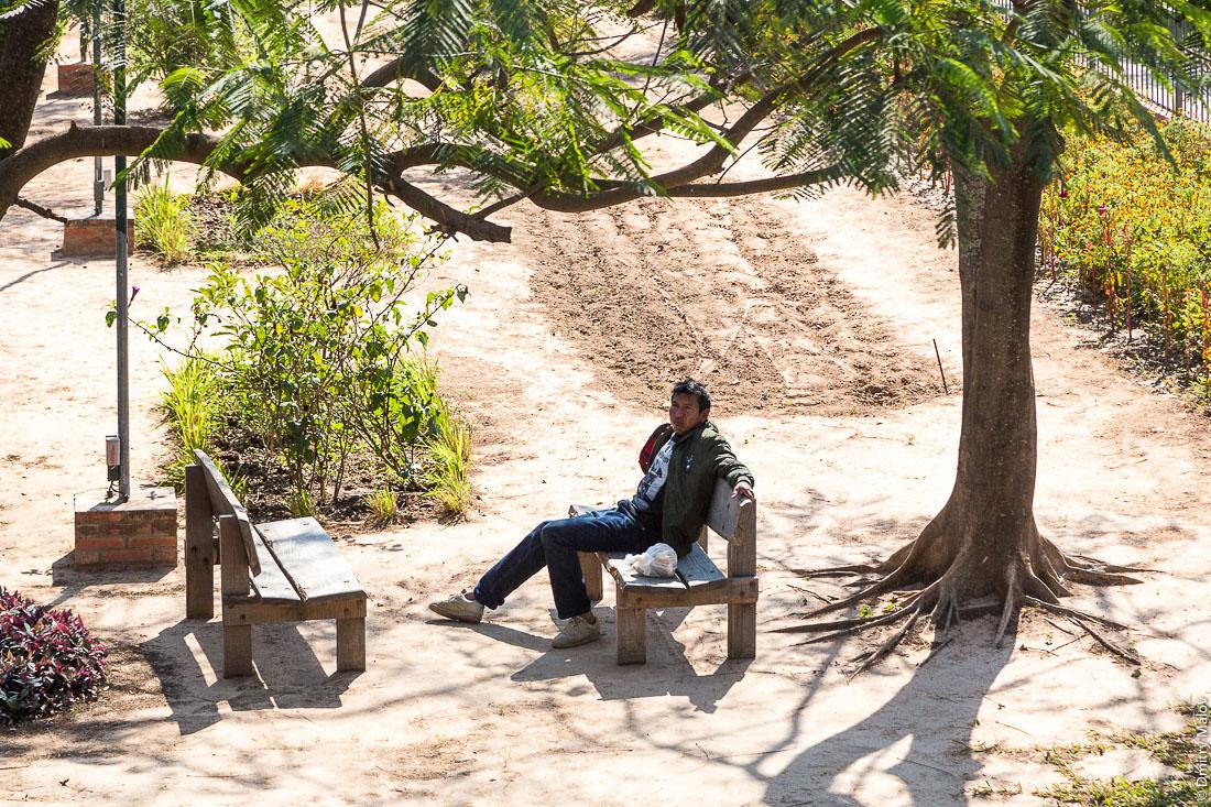 Местный индеец парагваец сидит в парке на самодельной скамейке, Филадельфия, Гран-Чако, Парагвай. Paraguayan native American man is sitting in the park on a bench, Filadelfia, Gran Chaco, Paraguay.