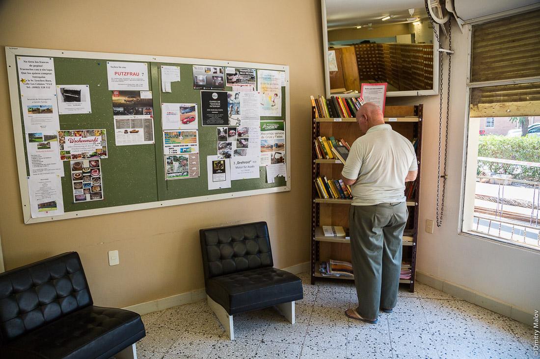 Мужчина обменной библиотечной полкой внутри почтового отделения в городе Филадельфия, Гран-Чако, Парагвай. A man checking Book Exchange / Public Bookshelves in a post office in the city of Filadelfia, Gran Chaco, Paraguay.