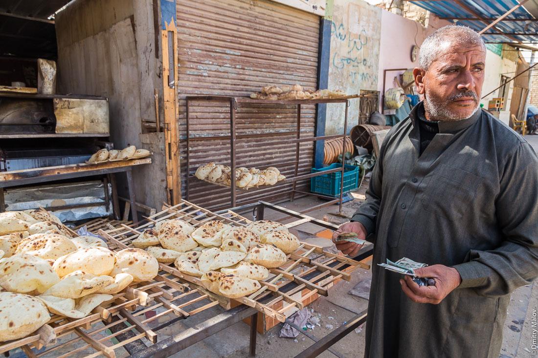 Bakery. A local arab man in national clothes buying pita bread, el-Bawiti, Oasis of Bahariya, Western Desert, Sahara, Egypt. Булочная, мужчина в местной национальной арабской одежде покупает хлеб пита. Эль-Бавити, Оазис Бахария, Западная пустыня, Сахара, Египет.
