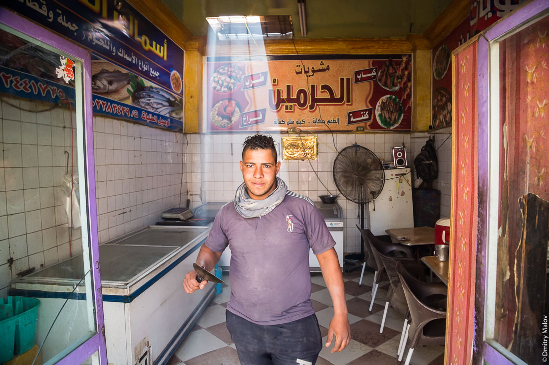 A man, a young guy with a spatula in a fish cafe. El-Bawiti, Oasis of Bahariya, Western Desert, Sahara, Egypt. Мужчина, молодой парень с кухонной лопаткой в рыбном кафе. Эль-Бавити, Оазис Бахария, Западная пустыня, Сахара, Египет.