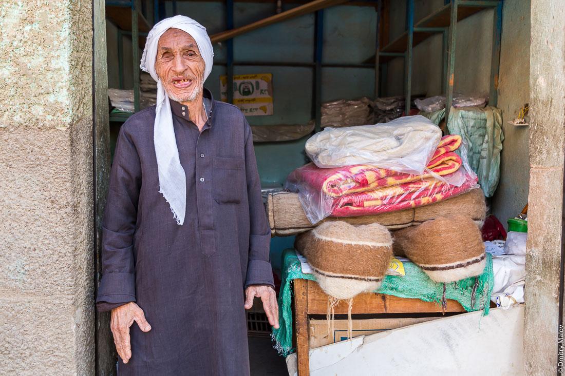 Old man dressed in a dark blue thawb (thobe) salling woolen blankets on a street of El-Bawiti town, Bahariya Oasis, Western desert, Sahara, Egypt. Старик в тёмно-синкй тобе продаёт шерстные одеяла на улице Эль-Бавити, Оазис Бахария, Западная пустыня, Сахара, Египет.