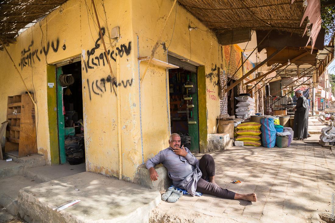 A man sits on pavement on a trade market street. El-Bawiti town, Bahariya Oasis, Western desert, Sahara, Egypt. Мужчина сидит на асфальте на тротуаре торговой улицы. Эль-Бавити, оазис Бахария, Западная пустыня, Сахара, Египет.