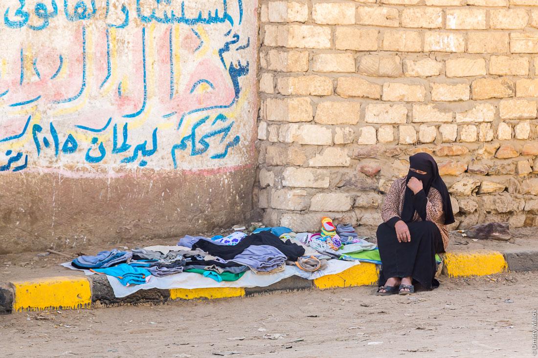 Арабская женщина-мусульманка в чёрном никабе торгует детской одеждой. Эль-Бавити, Оазис Бахария, Западная пустыня, Сахара, Египет. An Arab Muslim woman in a black nikab sells baby clothes. El-Bawiti, Oasis of Bahariya, Western Desert, Sahara, Egypt.