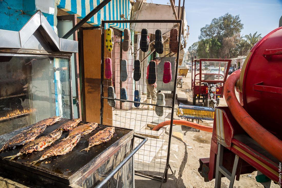 Assenisation machine nearby a fish restaurant. El-Bawiti, Oasis of Bahariya, Western Desert, Sahara, Egypt.  Ассенизационная машина рядом с рыбным рестораном. Эль-Бавити, Оазис Бахария, Западная пустыня, Сахара, Египет.