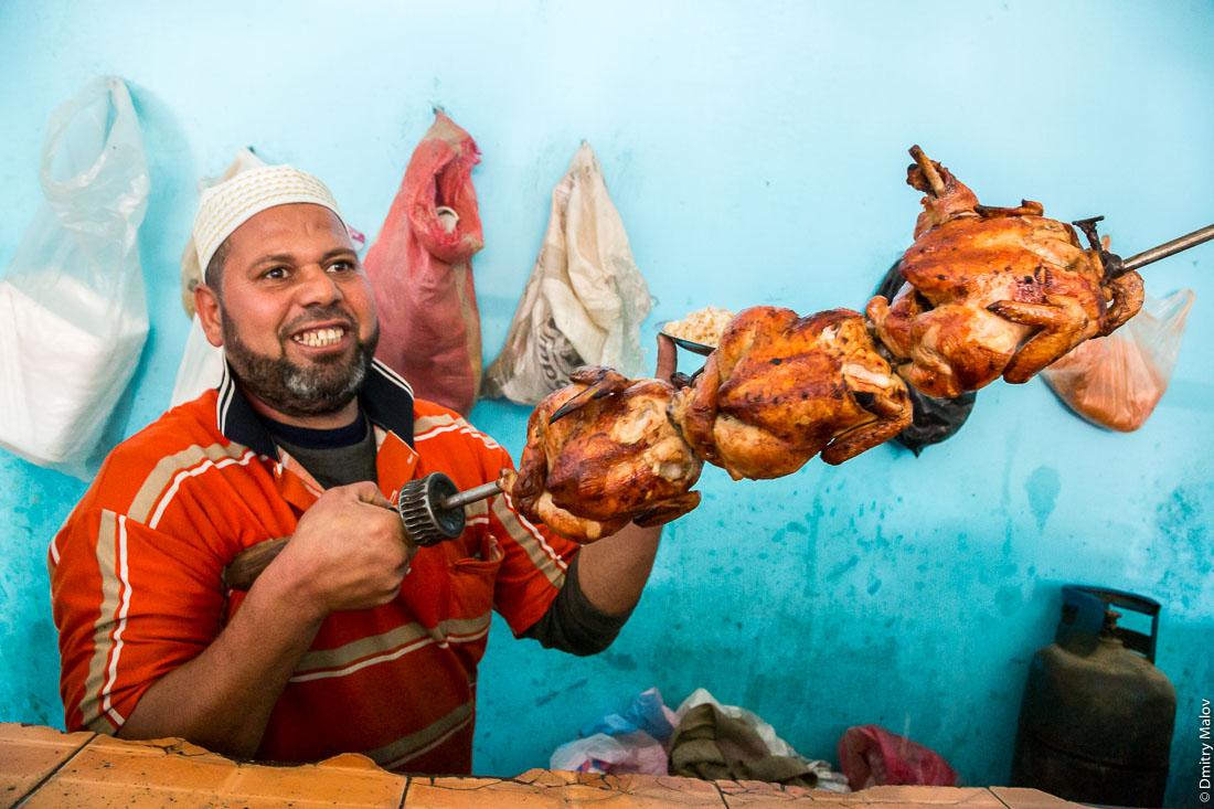 A father chef brought ready cooked grilled fried three chickens from kitchen to customers. El-Bawiti, Oasis of Bahariya, Western Desert, Sahara, Egypt. Шеф-повар выносит готовую жареную курицу с кухни клиентам.  Эль-Бавити, Оазис Бахария, Западная пустыня, Сахара, Египет.