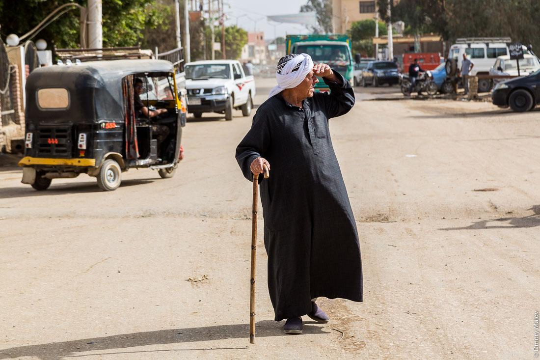 Old man dressed in a black thawb (thobe) with a stick of a street of El-Bawiti town, Bahariya Oasis, Western desert, Sahara, Egypt. Старик в чёрной тобе с палкой-посохом на улице Эль-Бавити, Оазис Бахария, Западная пустыня, Сахара, Египет.