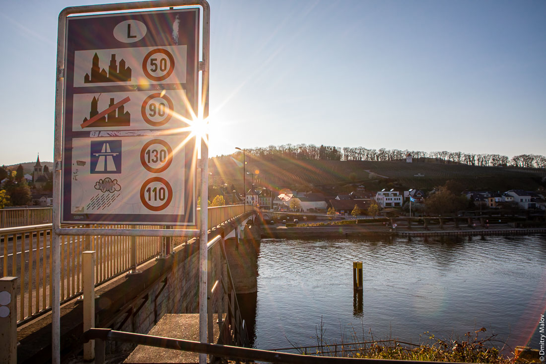 The local border Moselle bridge between Schengen, Luxembourg and Perl, Germany. A road sign for speed limit while crossing to a new country. Местный пограничный мост через Мозель между Шенгеном, Люксембург и Перлом, Германия.