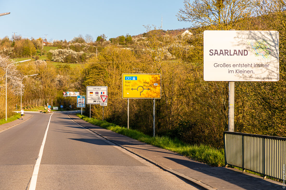 The Germany border Perl, Germany near local border Moselle bridge between Schengen, Luxembourg. Road signs, including Saarland Großes entsteht immersions im Kleinen. Граница Германии в Перле, около местного пограничного моста через Мозель c Шенгеном, Люксембург. Дорожные знаки